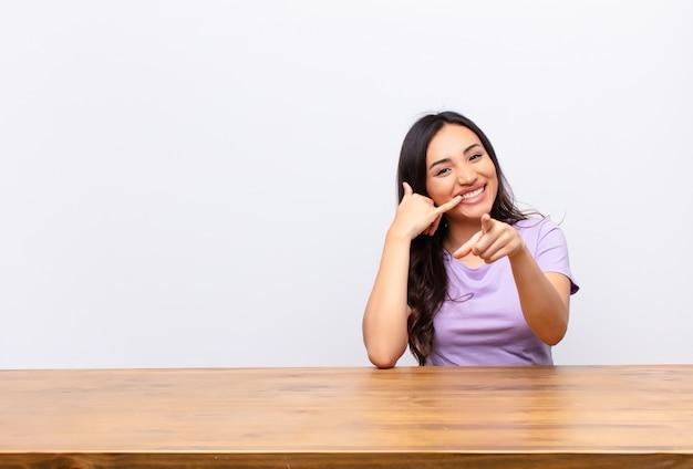 Kobieta uśmiechając się wesoło i wskazując z przodu, wykonując połączenie, gestem później, rozmawia przez telefon