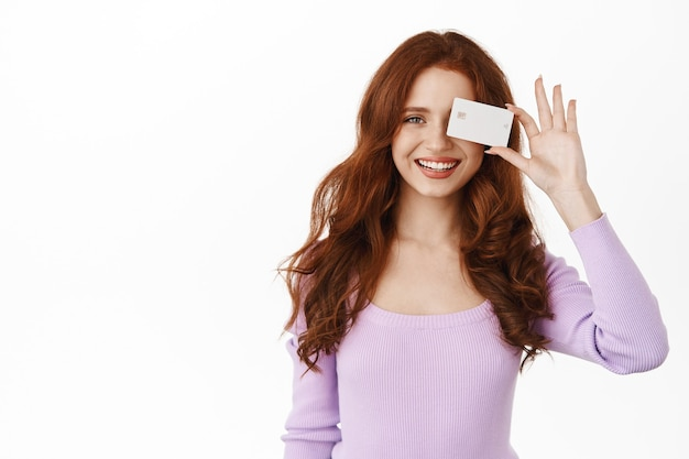Kobieta uśmiechnięta, białe zęby, pokazująca bankową kartę kredytową, płatność zbliżeniowa, stojąca na białym