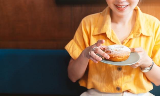 Kobieta uśmiechnięta i ubrana w żółtą koszulkę trzymająca bladozielony talerz pączka z lukrem w cukrze i pokazujący go w nowoczesnej kawiarni.