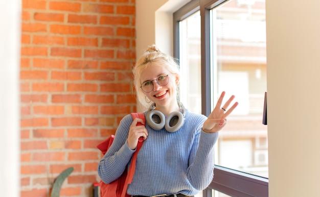 Kobieta uśmiechnięta i wyglądająca przyjaźnie, pokazująca cyfrę trzy lub trzecią z ręką do przodu, odliczająca
