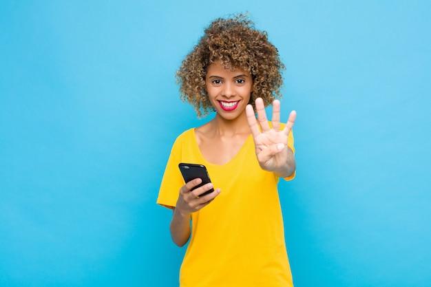 Kobieta uśmiechnięta i wyglądająca przyjaźnie, pokazująca numer cztery lub czwarty ręką do przodu, odliczająca