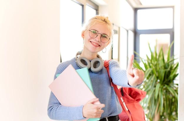 Kobieta uśmiechnięta i wyglądająca przyjaźnie, pokazująca numer jeden lub pierwszy z ręką do przodu, odliczająca