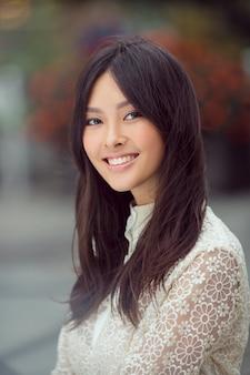 Kobieta uśmiechnięta - portret szczęśliwy, piękny i piękny rasy mieszanej rasy azjatyckiej młodej kobiety
