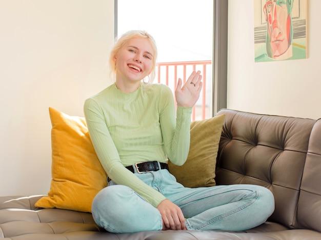 Kobieta uśmiechnięta radośnie i radośnie, machająca ręką, witająca cię i pozdrawiająca lub żegnająca się