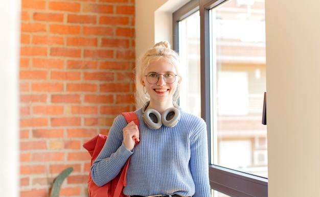 Kobieta uśmiechnięta radośnie z ręką na biodrze i pewną siebie, pozytywną, dumną i przyjazną postawą