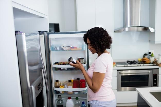 Kobieta usuwa butelkę z lodówki w kuchni