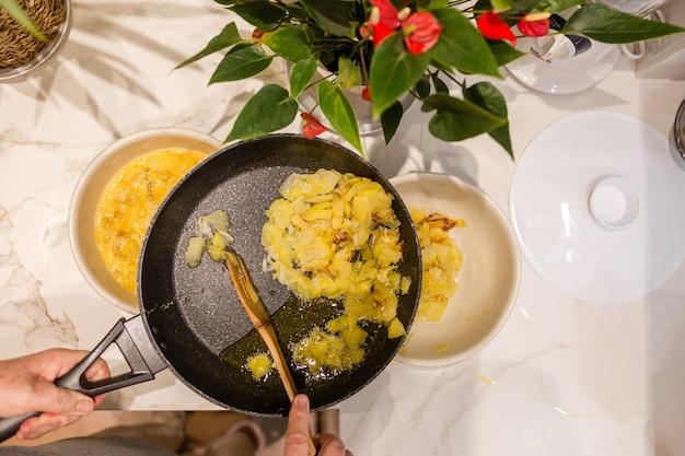 Kobieta usuwa nadmiar oleju z ziemniaków z cebulą, aby ugotować omlet ziemniaczany