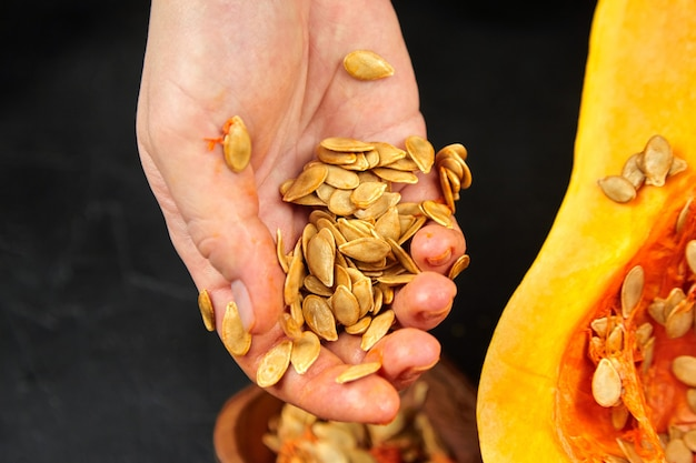 Kobieta usuwa pestki dyni i żylaste włókna. gotowanie słodkiej dyni zimowej, jesienna resipe. dynia piżmowa, kobiece dłonie z połową dyni na czarnym tle, zbliżenie, selektywne focus