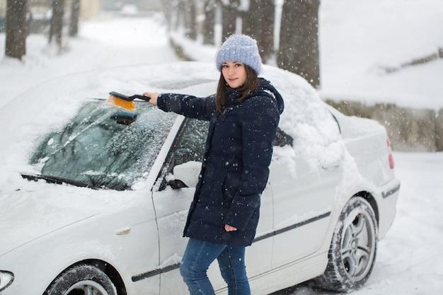 Kobieta usuwa śnieg z przedniej szyby samochodu