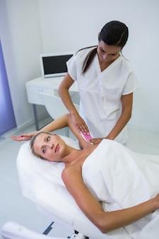 Kobieta usuwa włosy pod pachą