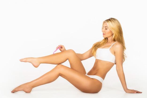 Kobieta usuwanie włosów na nogach brzytwą. kobieta do golenia nóg w łazience.