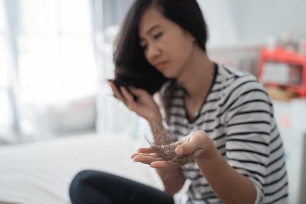 Kobieta uszkadza wypadanie włosów