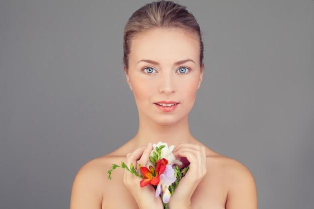 Kobieta uzdrowiska. zdrowa kobieta z jasną skórą i kwiatami. koncepcja pielęgnacji skóry