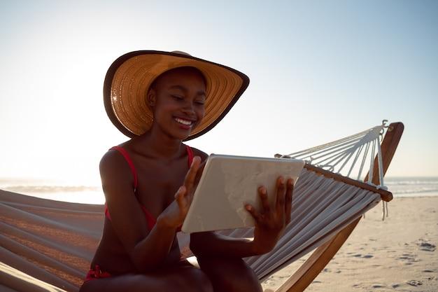 Kobieta używa cyfrową pastylkę podczas gdy relaksujący w hamaku na plaży