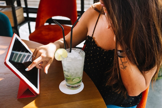 Kobieta używa cyfrową pastylkę z mojito na drewnianym stole w restauraci