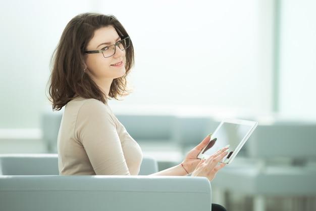 Kobieta używa cyfrowego tabletu, siedząc w biurze