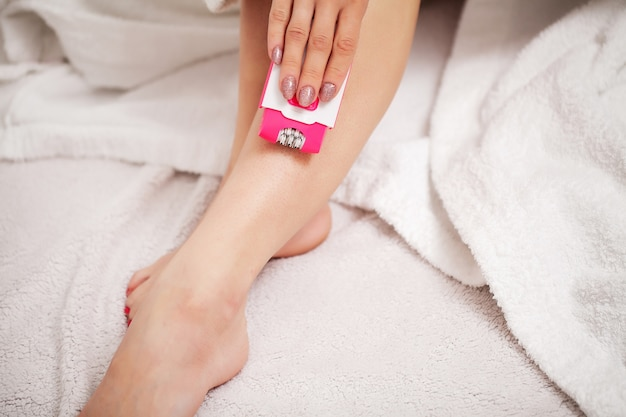 Kobieta używa depilatora do usuwania włosów na nogach w łazience w mieszkaniu domowym