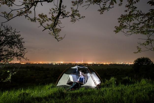 Kobieta używa jej laptop w campingu przy nocą