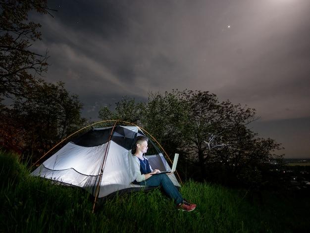 Kobieta używa jej laptop z słuchawki w campingu przy nocą.