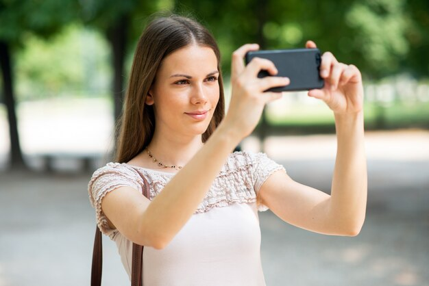 Kobieta używa jej telefon komórkowego brać fotografię