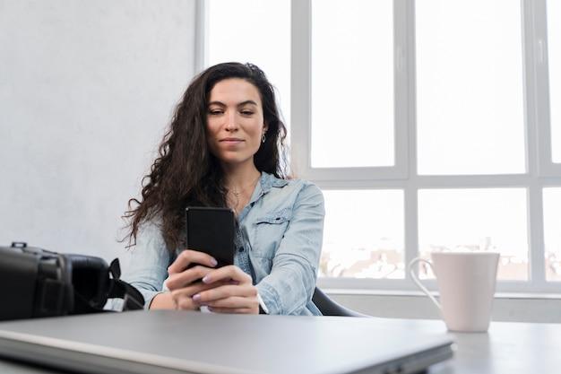 Kobieta używa jej telefon komórkowego w biznesowym biurze