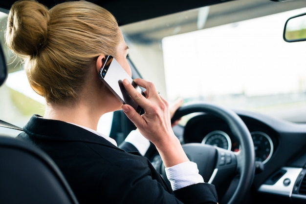 Kobieta używa jej telefon podczas gdy jadący samochód