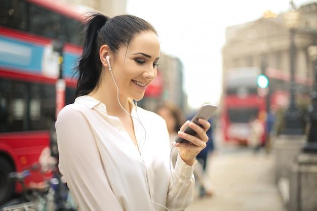 Kobieta używa jej telefon podczas gdy słuchający z słuchawkami