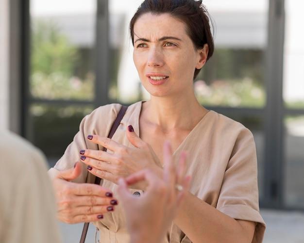 Kobieta używa języka migowego do rozmowy z kimś na zewnątrz