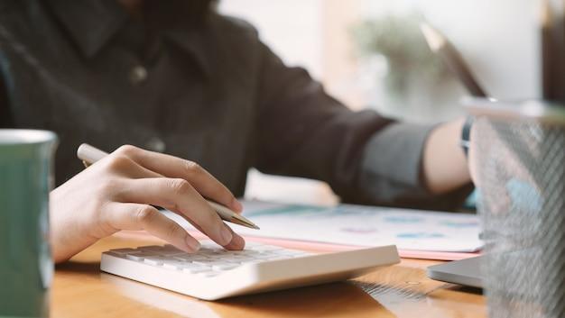 Kobieta używa kalkulatora do finansów i rachunkowości analizuj budżet finansowy