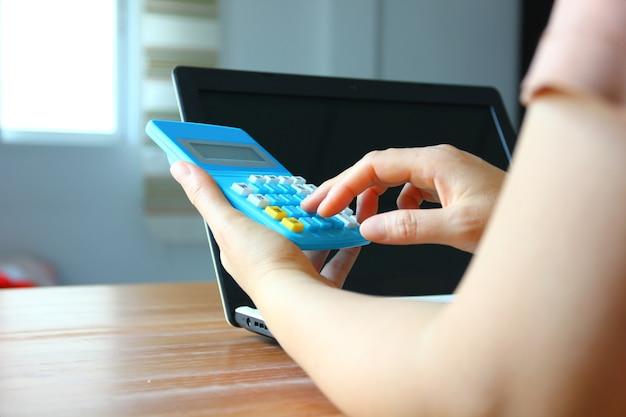 Kobieta używa kalkulatora whie pracującego w domu z laptopem