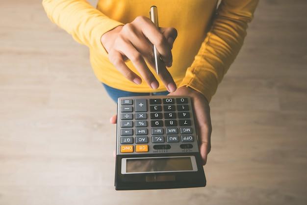Kobieta używa kalkulatora z piórem w jej ręce