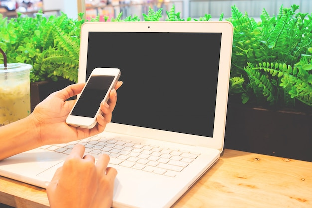 Kobieta używa laptop i używać smartphone.