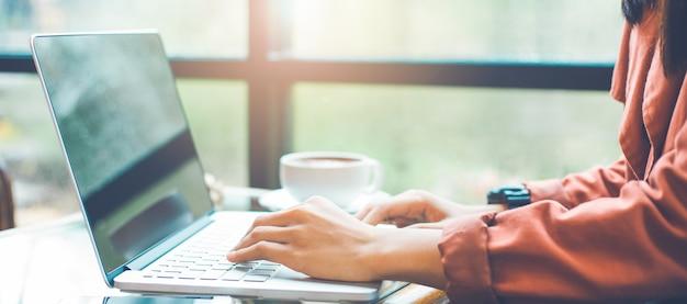 Kobieta używa laptop. kobieta pracuje na laptopie w kawiarni.