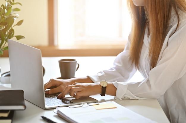 Kobieta używa laptop na stole z cropped strzał fotografią.
