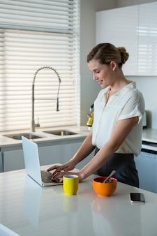 Kobieta używa laptop w kuchni