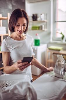 Kobieta używa mądrze telefon podczas gdy prasujący odziewa