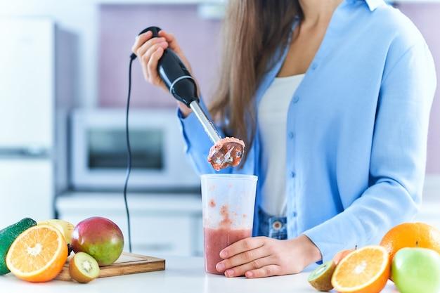 Kobieta używa miksera ręcznego do mieszania świeżych owoców w celu przygotowania diety detox smoothie w kuchni w domu