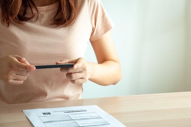 Kobieta używa mobilnego smartfona do zeskanowania kodu qr z faktury w dokumentach do rachunków. koncepcja płatności i skanowania