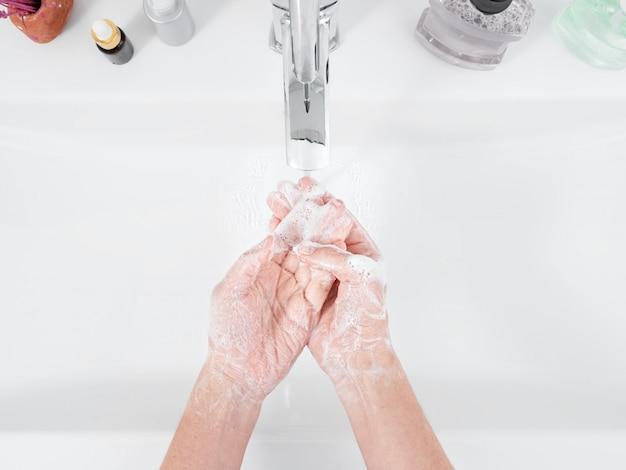 Kobieta używa mydła i myje ręce pod bieżącą wodą. pojęcie higieny, widok z góry, opieka zdrowotna. higiena osobista i pielęgnacja ciała