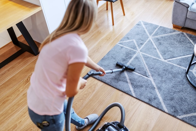 Kobieta używa odkurzacz w domu.
