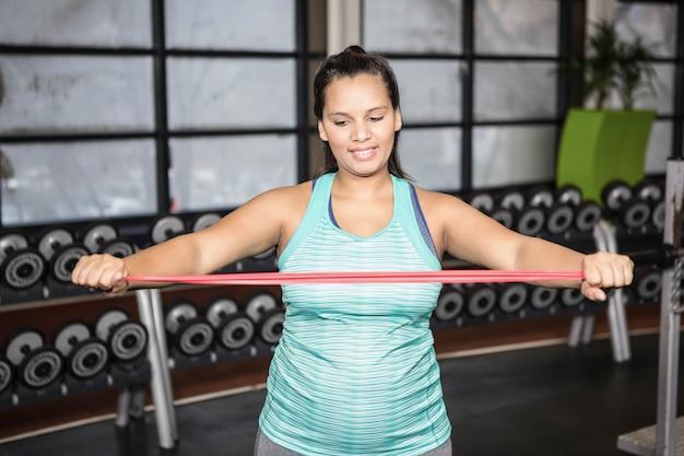 Kobieta używa oporu zespołu w gym