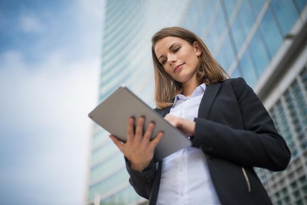 Kobieta używa pastylkę przed jej biurem