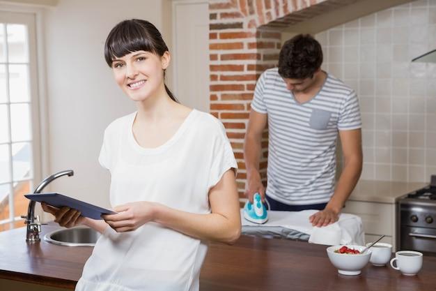 Kobieta używa pastylkę w kuchni podczas gdy mężczyzna odprasowywa koszula