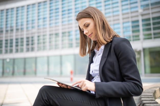 Kobieta używa pastylkę z jej biura