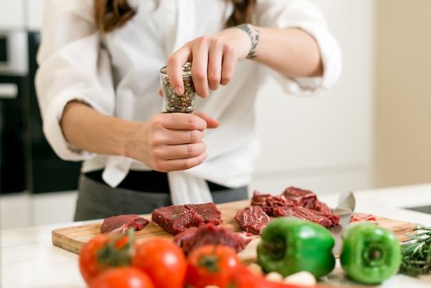 Kobieta używa pikantność gotować czerwonego mięso z warzywami na kuchni