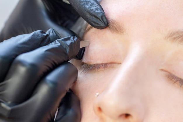 Kobieta używa pincety na cierpliwej brwi przy zdrowie zdrojem