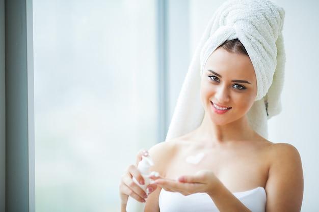 Kobieta używa produktów do pielęgnacji skóry w domu w jasnej łazience