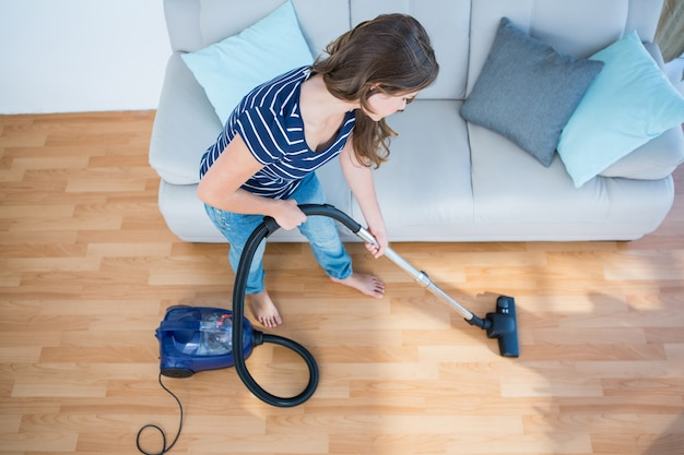 Kobieta używa próżniowego cleaner na drewnianej podłoga