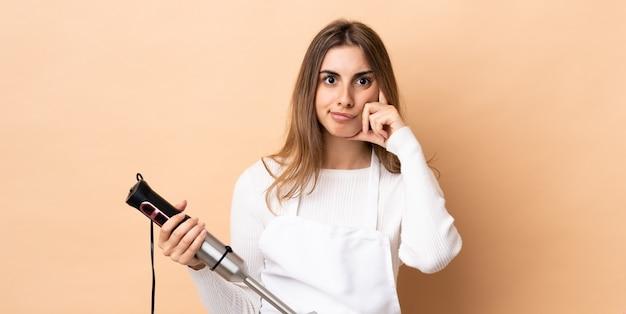 Kobieta używa ręki blender nad odosobnioną ścianą myśleć pomysł