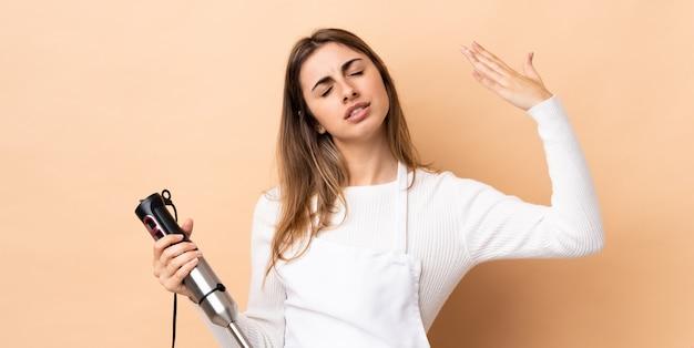 Kobieta używa ręki blender nad odosobnioną ścianą z zmęczonym i chorym wyrażeniem